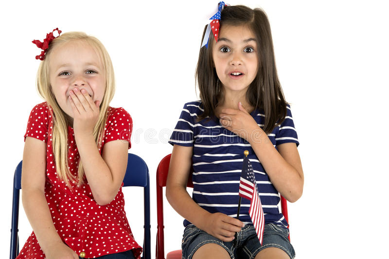 Patriotic girls holding an American flag with funny expressions stock images