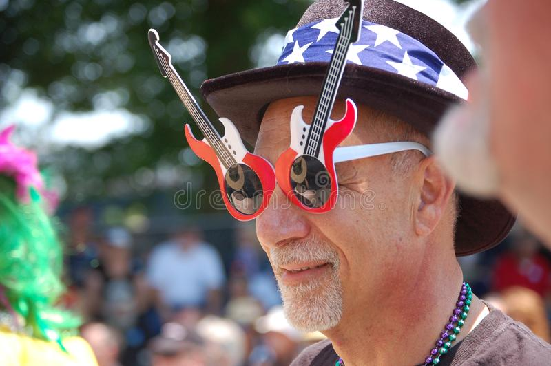 Patriotic Guitar Glasses in Portland, OR. An elderly man wears patriotic guitar sunglasses at the Safeway Blues Festival in Portland, Oregon. The annual event is stock photos