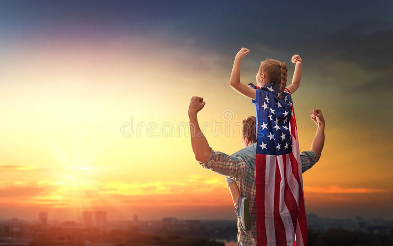 Patriotic holiday. Happy family. Father and his daughter child girl with American flag outdoors on background sunset cityscape. USA celebrate 4th of July royalty free stock photography