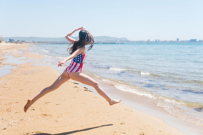 Patriotic jump US on the sandy shore of the ocean stock images
