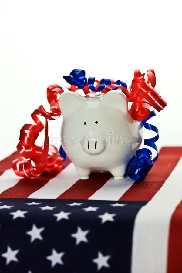 Patriotic piggy bank. With red and white ribbons on the American flag with an isolated white background stock photography