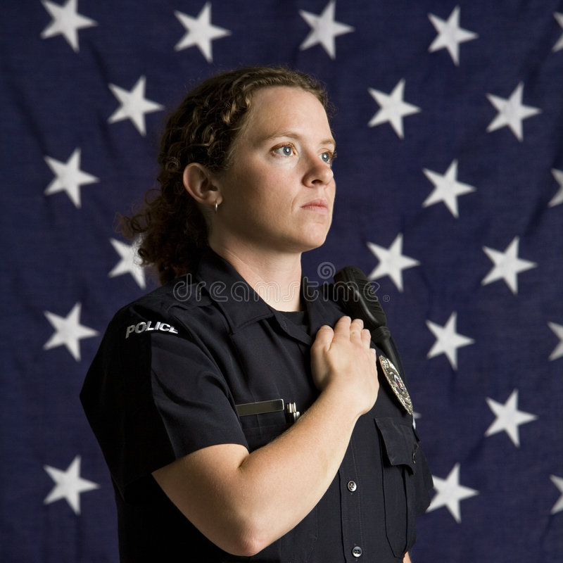 Patriotic policewoman. Portrait of mid adult Caucasian policewoman pledging allegiance with American flag as backdrop stock photos