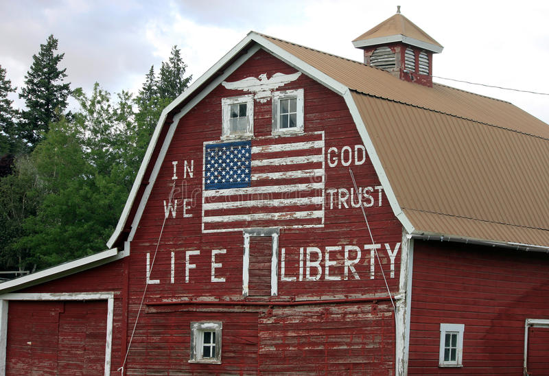 Patriotic Red Barn with Painted American Flag. And In God We Trust stock photo
