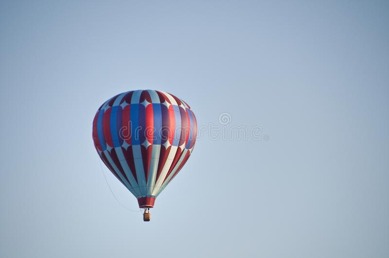 Patriotic red white and blue hot-air balloon taking off into the blue morning sky royalty free stock image