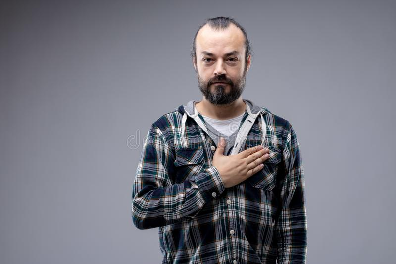 Patriotic or sincere man placing hand on heart stock photos