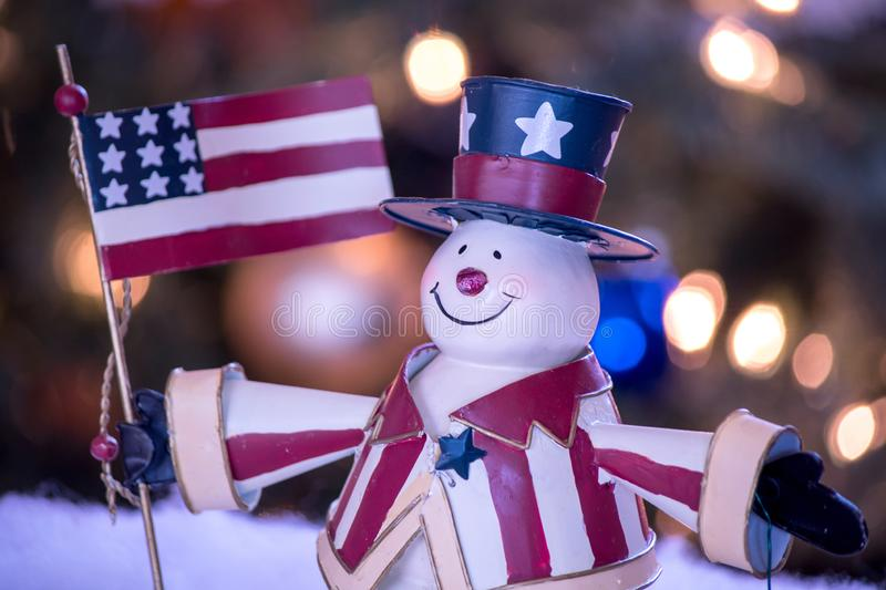 Close up of patriotic snowman. Patriotic snowman in red white and blue, with arms wide open and an American flag royalty free stock image