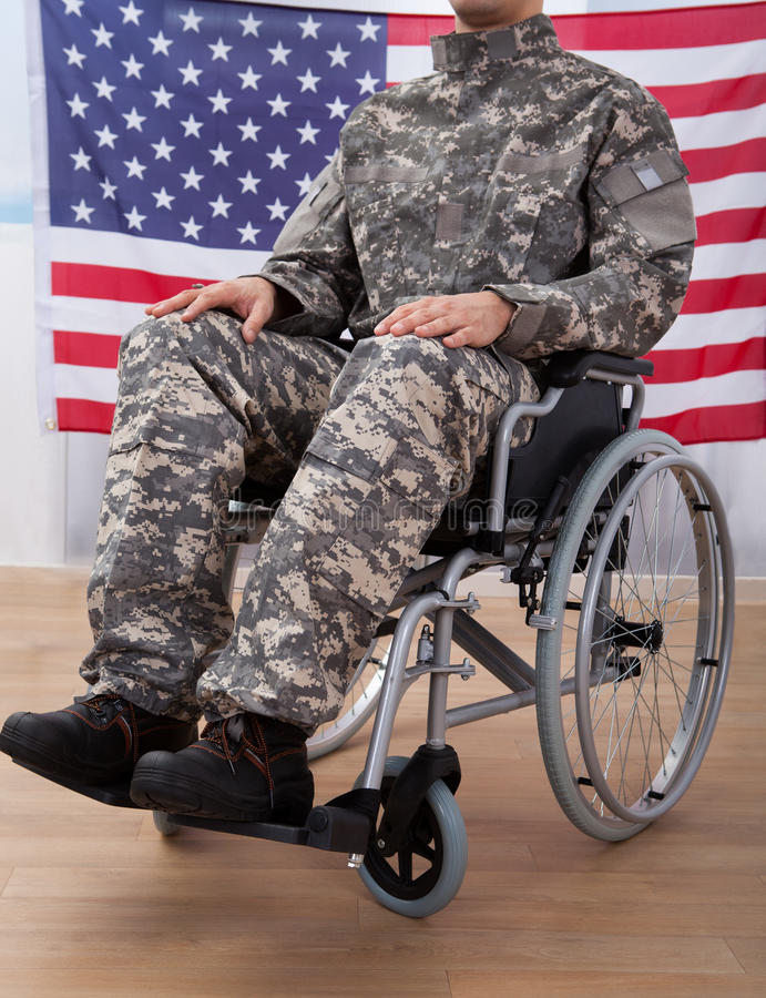Patriotic Soldier Sitting On Wheel Chair Against American Flag. Cropped image of patriotic soldier sitting on wheel chair against American flag stock images