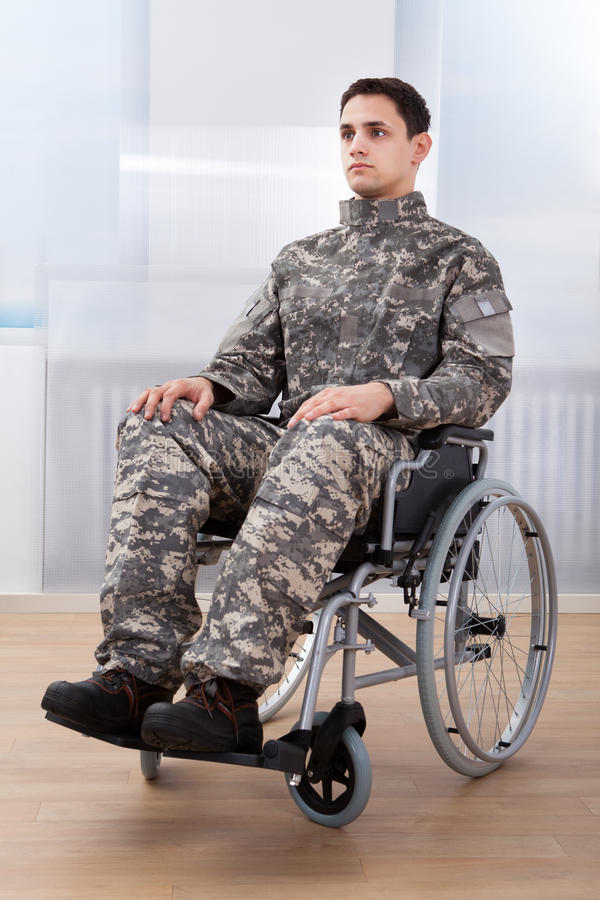 Patriotic soldier sitting on wheel chair. Full length of patriotic soldier sitting on wheel chair at home stock photography