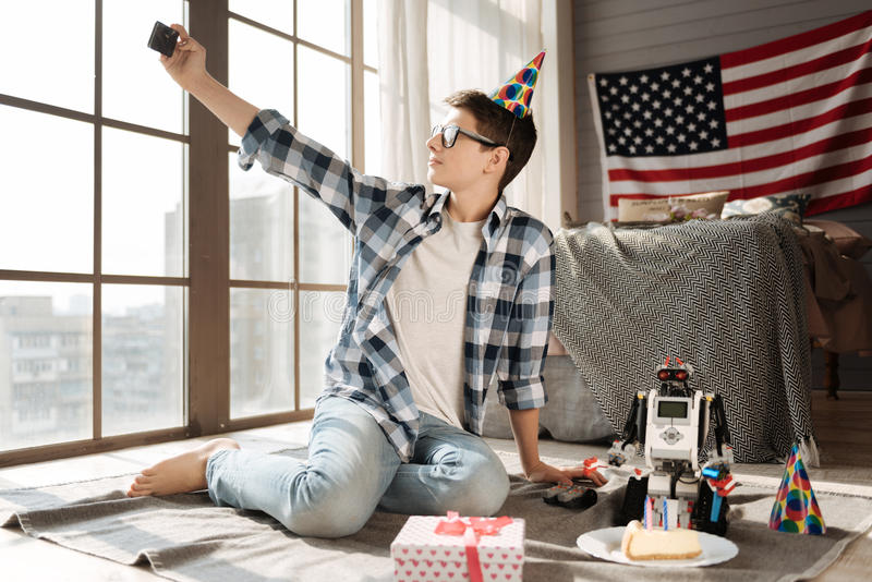 Patriotic teenager looking at panoramic window. Fix the moment. Serious boy wearing checked shirt sitting near his robot while posing on camera stock image