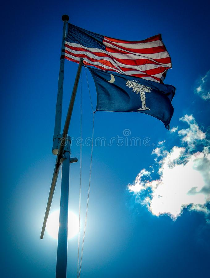 US Flag flying over South carolina state flag waving in wind on a sunny day in front of blue sky royalty free stock images
