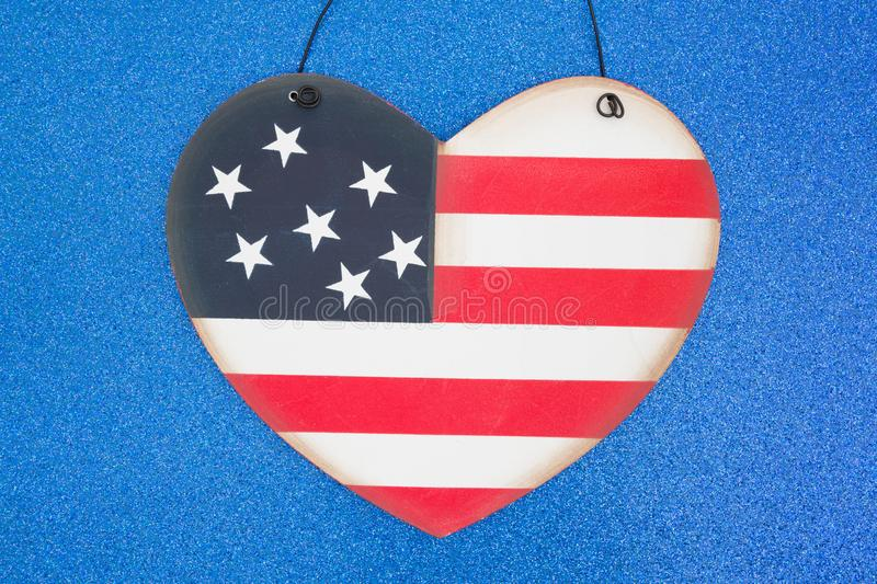 Patriotic USA flag heart on blue. Patriotic USA stars and stripes flag heart on sparkling blue royalty free stock photo