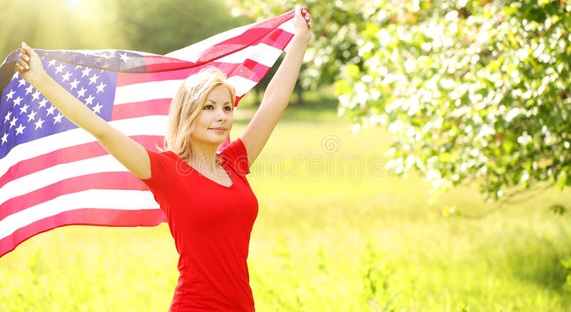 Patriotic young woman with American flag royalty free stock image