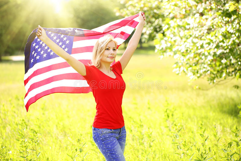 Patriotic young woman with American flag stock images