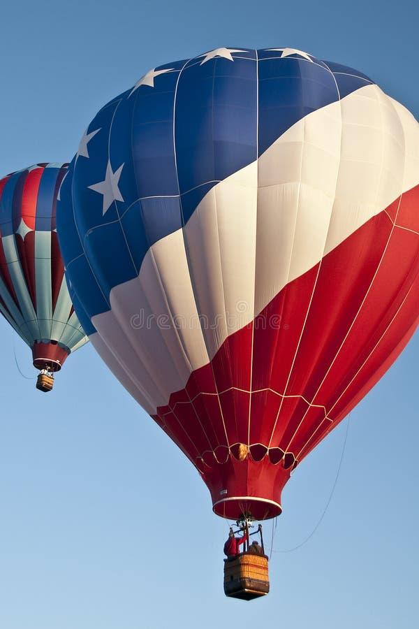 Patriotisch roter, weißer und blauer Heißluftballon, der mit vielen anderen Heißluftballons in den blauen MorgenHimmel abhebt lizenzfreies stockfoto