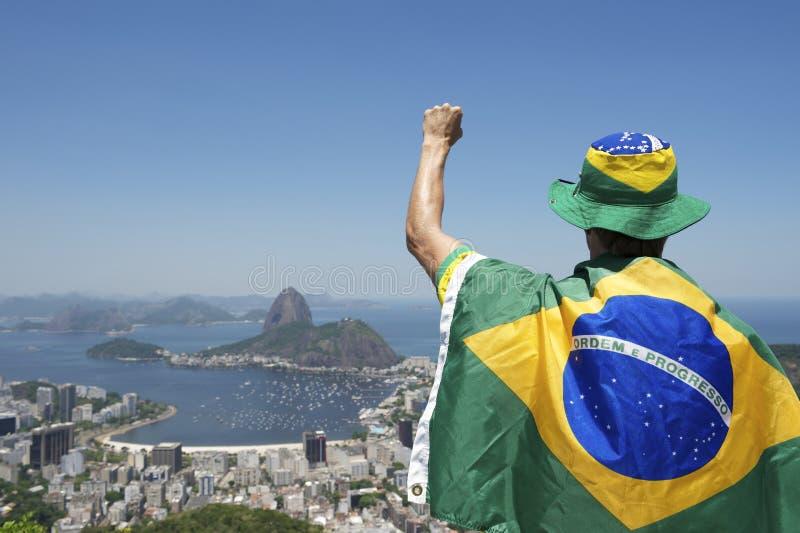Patriotische Brasilien-Fan-Stellung eingewickelt in der brasilianischen Flagge Rio stockfotografie