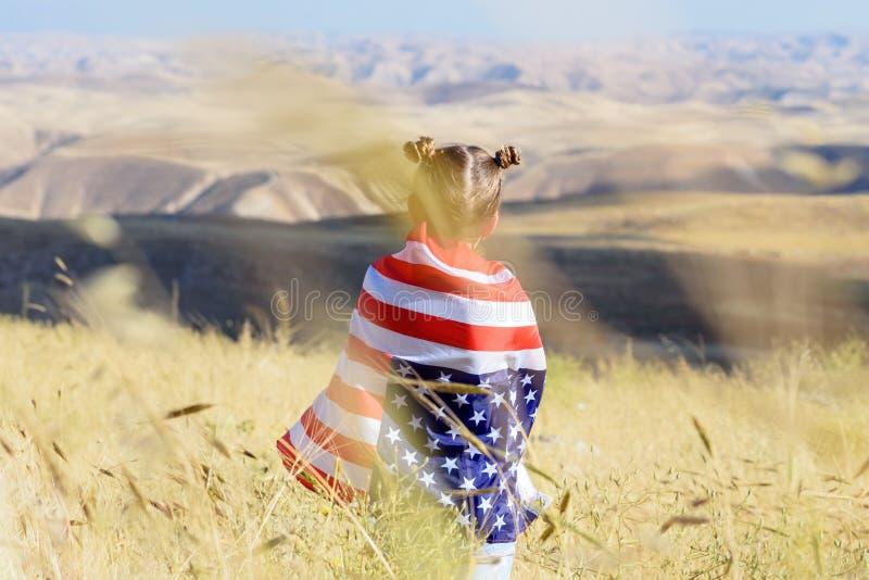 Patriotischer Feiertag Gl?ckliches Kind, nettes kleines Kinderm?dchen mit amerikanischer Flagge USA feiern Juli 4. stockbild