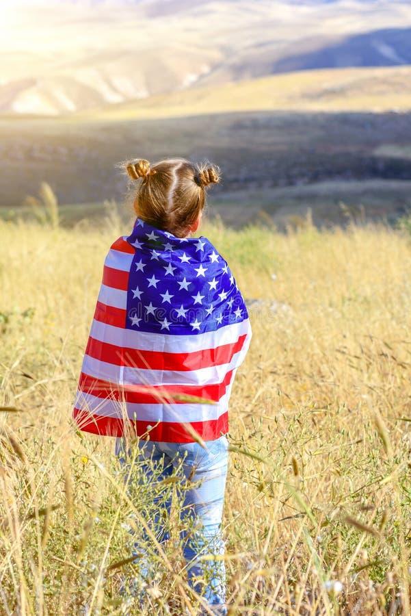 Patriotischer Feiertag Gl?ckliches Kind, nettes kleines Kinderm?dchen mit amerikanischer Flagge USA feiern Juli 4. stockfotografie
