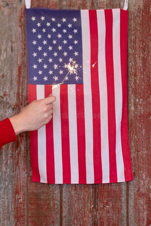 Patriotischer Hintergrund mit roter Scheunentür, -flagge und -Wunderkerzen stockfotografie