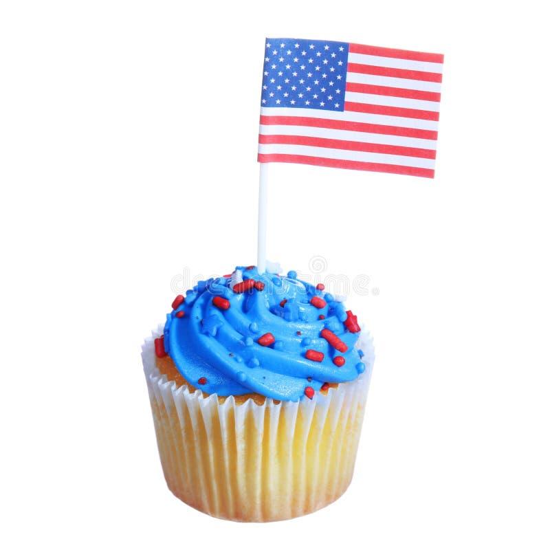 Patriotischer kleiner Kuchen mit amerikanischer Flagge und blauen Creme- und Rotensternen besprüht auf die Oberseite, lokalisiert  stockbilder
