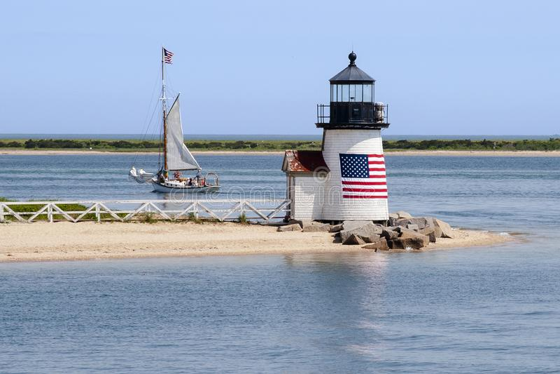 Patriotischer Leuchtturm führt ein Segelboot aus Nantucket-Insel H heraus lizenzfreies stockfoto
