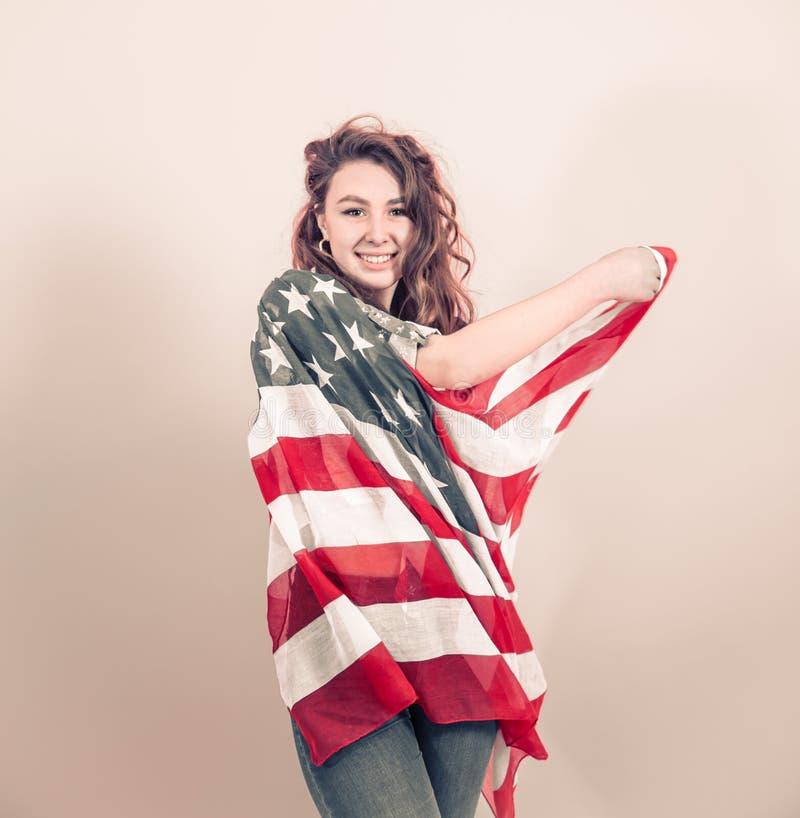 Patriotisches Mädchen mit der Flagge von Amerika auf einem farbigen Hintergrund stockbilder