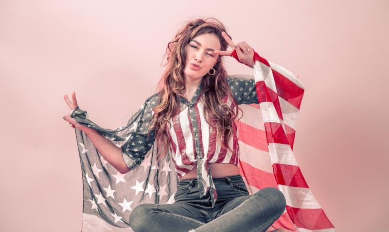 Patriotisches Mädchen mit der Flagge von Amerika auf einem farbigen Hintergrund stockbild