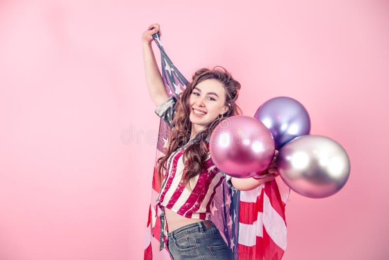 Patriotisches Mädchen mit der Flagge von Amerika auf einem farbigen Hintergrund lizenzfreie stockfotografie