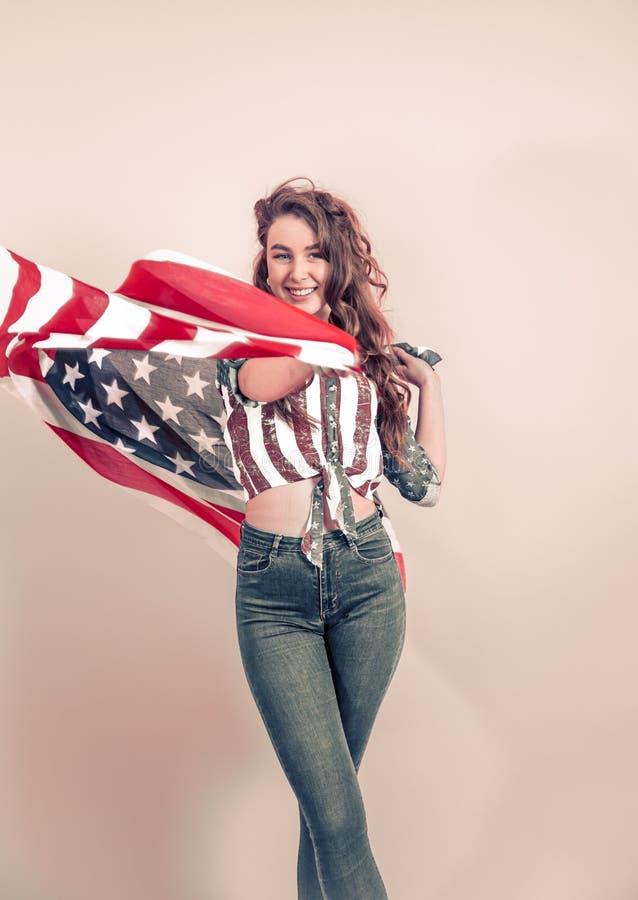 Patriotisches M?dchen mit der Flagge von Amerika auf einem farbigen Hintergrund lizenzfreies stockfoto
