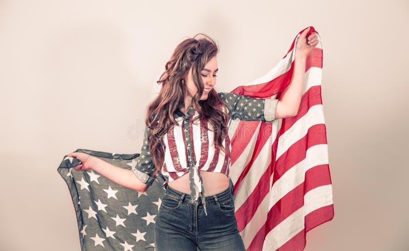 Patriotisches M?dchen mit der Flagge von Amerika auf einem farbigen Hintergrund lizenzfreie stockfotografie