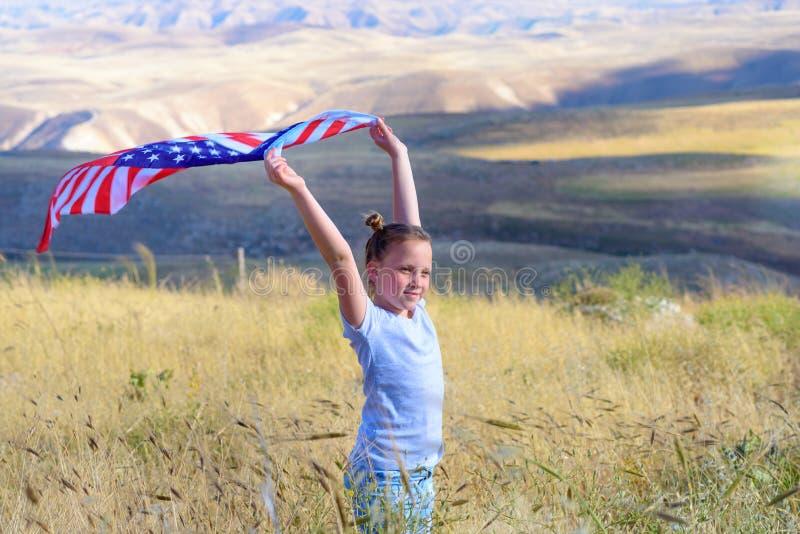 Patriotisk ferie Lycklig unge, gullig flicka f?r litet barn med amerikanska flaggan Medborgare 4 juli isolerad minnes- white f?r  arkivfoto