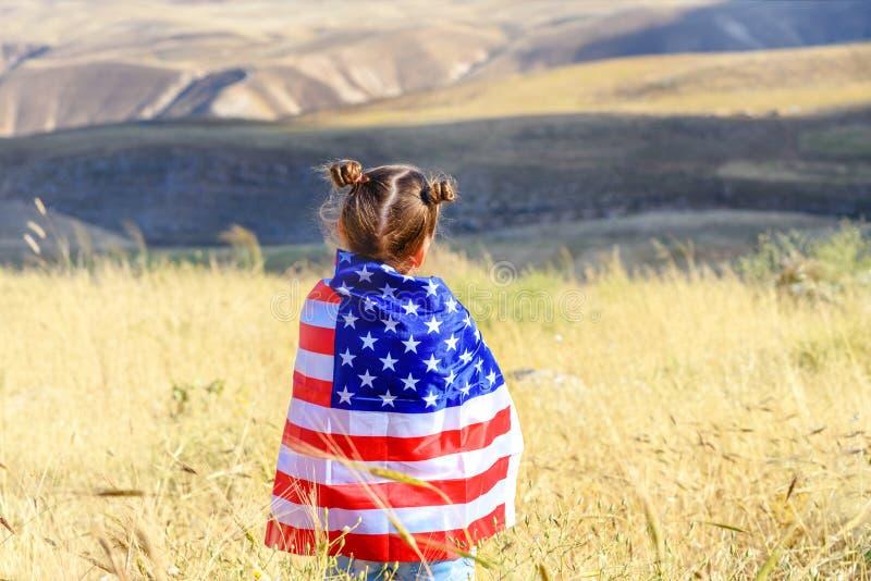 Patriotisk ferie Lycklig unge, gullig flicka f?r litet barn med amerikanska flaggan USA firar 4th Juli royaltyfri bild
