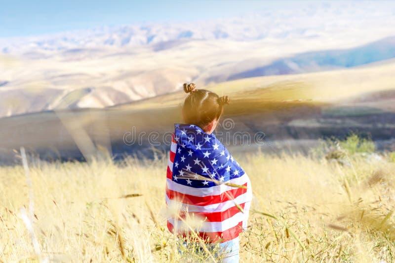 Patriotisk ferie Lycklig unge, gullig flicka f?r litet barn med amerikanska flaggan USA firar 4th Juli royaltyfria bilder