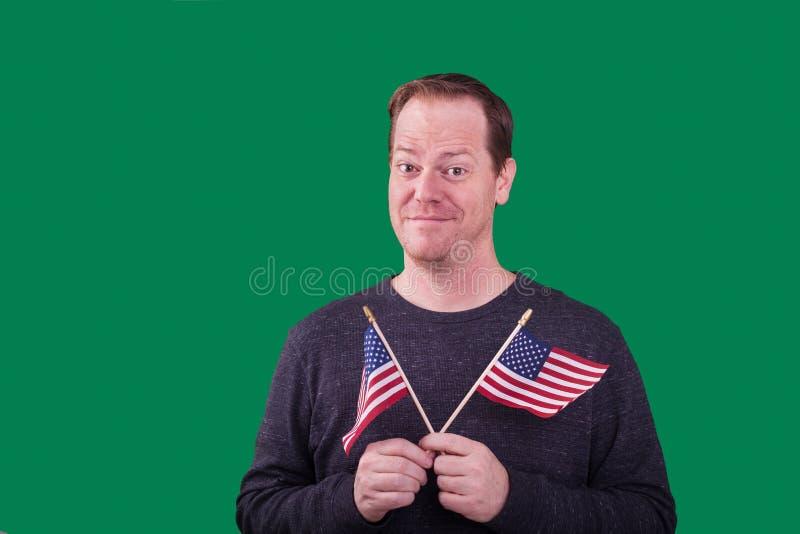Patriotisk man som rymmer två amerikanska flaggan royaltyfria bilder