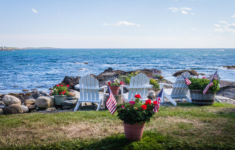 Patriotiska inlagda blommor ses bland vita adirondackstolar som förbiser den härliga blåttfjärden royaltyfri fotografi