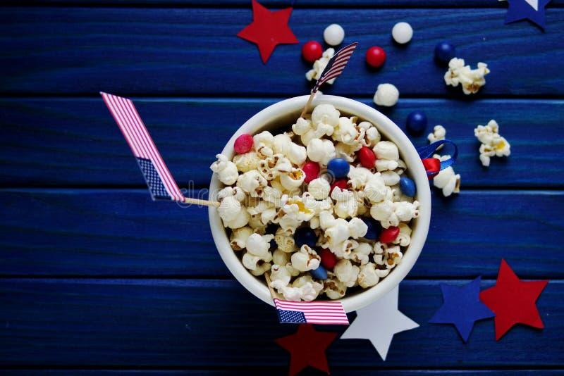 Patriotiskt popcorn på Juli 4 i en vit hink med amerikanska flaggan på en blå träbakgrund USA-självständighetsdagen royaltyfria bilder