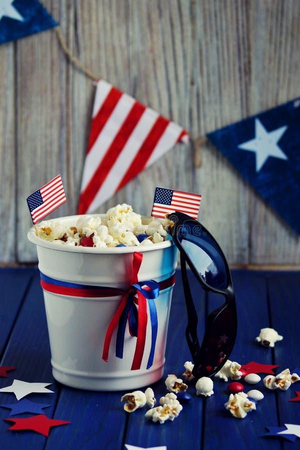 Patriotiskt popcorn på Juli 4 i en vit hink med amerikanska flaggan på en blå träbakgrund USA-självständighetsdagen arkivfoton
