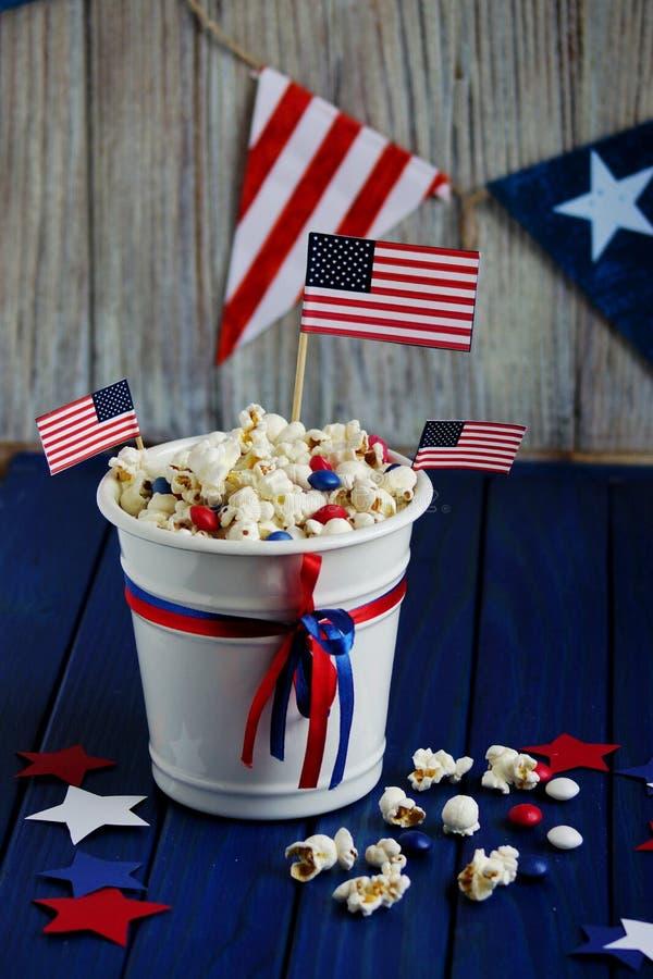Patriotiskt popcorn på Juli 4 i en vit hink med amerikanska flaggan på en blå träbakgrund USA-självständighetsdagen arkivbilder
