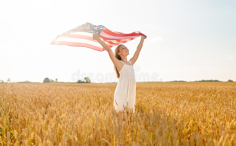 Girl with american flag waving over cereal field. Patriotism, independence day and country concept - happy smiling young girl holding national american flag royalty free stock images
