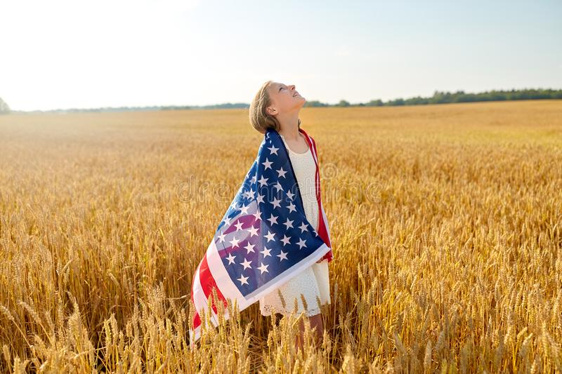 Happy girl in american flag on cereal field. Patriotism, independence day and country concept - happy smiling young girl wrapped into national american flag on stock image