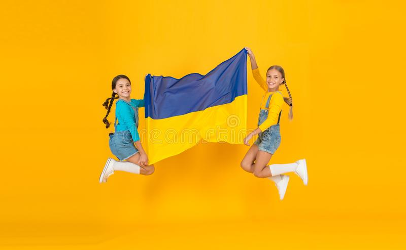 Patriotism respect and love to motherland. National identity concept. Girls with blue and yellow flag. Patriotic. Education. Happy independence day. Children royalty free stock image