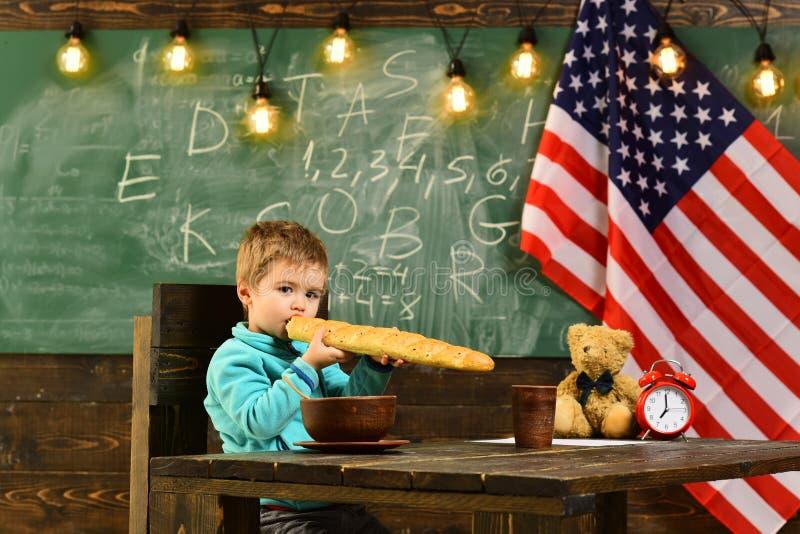 Patriotisme et liberté Le petit garçon mangent du pain au drapeau américain au jour de la connaissance Instruisez l'enfant à la l photographie stock