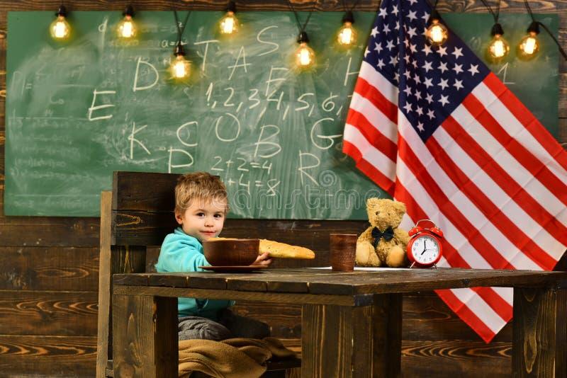 Patriotismus und Freiheit Kleiner Junge essen Brot an der amerikanischen Flagge am Wissenstag Glücklicher Unabhängigkeitstag der  lizenzfreies stockbild