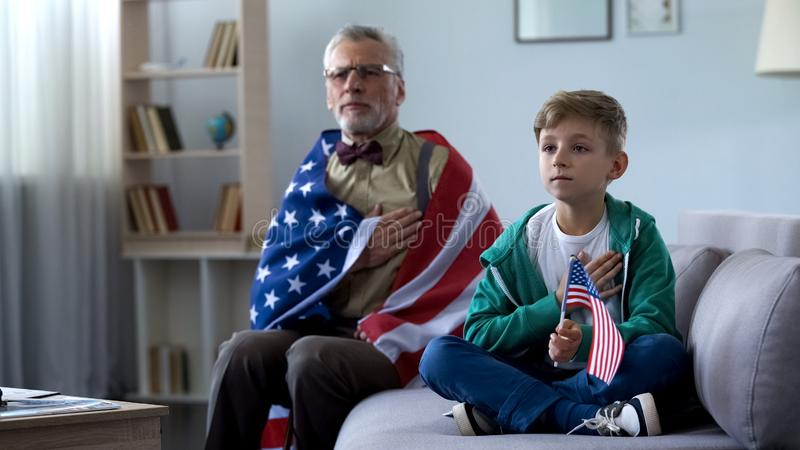 Patriottische oude mens die Amerikaanse vlag, het luisteren volkslied met kleinzoon houden stock foto