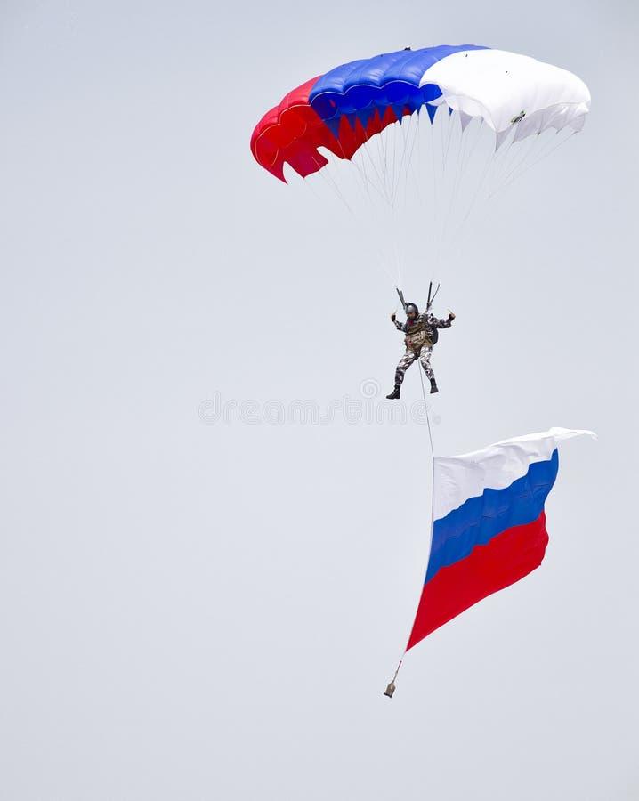 Patriottische vlucht van een parachutist met de Russische vlag stock fotografie