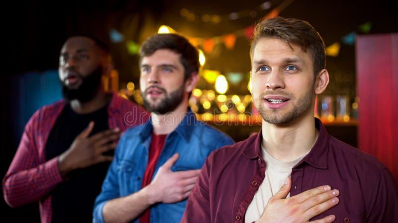 Patriottische voetbalventilators die aan volkslied, het letten op spel in bar luisteren stock foto's