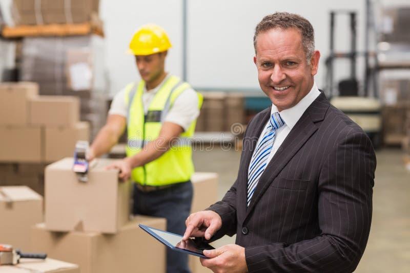 Patron à l'aide du comprimé numérique dans l'entrepôt image libre de droits