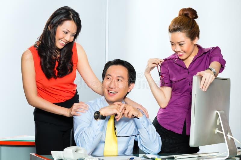 Patron asiatique de coureur de jupons flirtant au bureau photo libre de droits