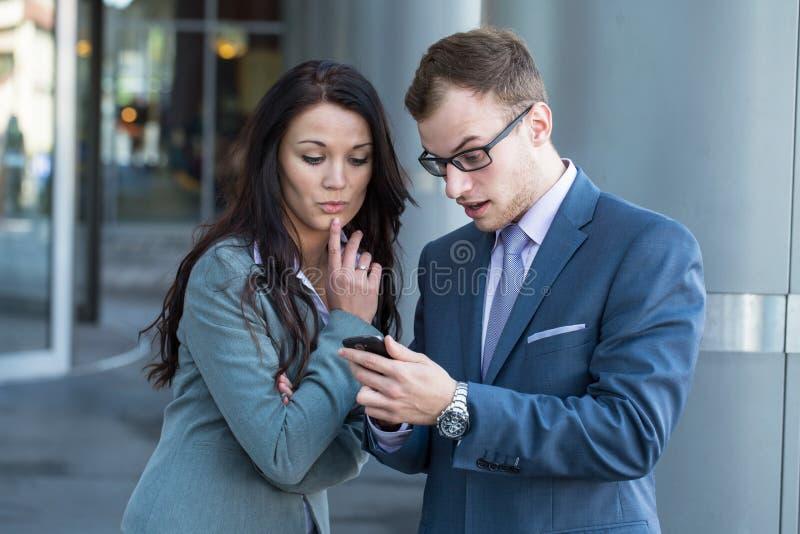 Patron avec le téléphone portable et son secrétaire. Soyez déçu. photo stock