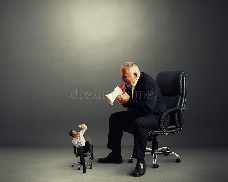 Patron criant au petit travailleur image stock
