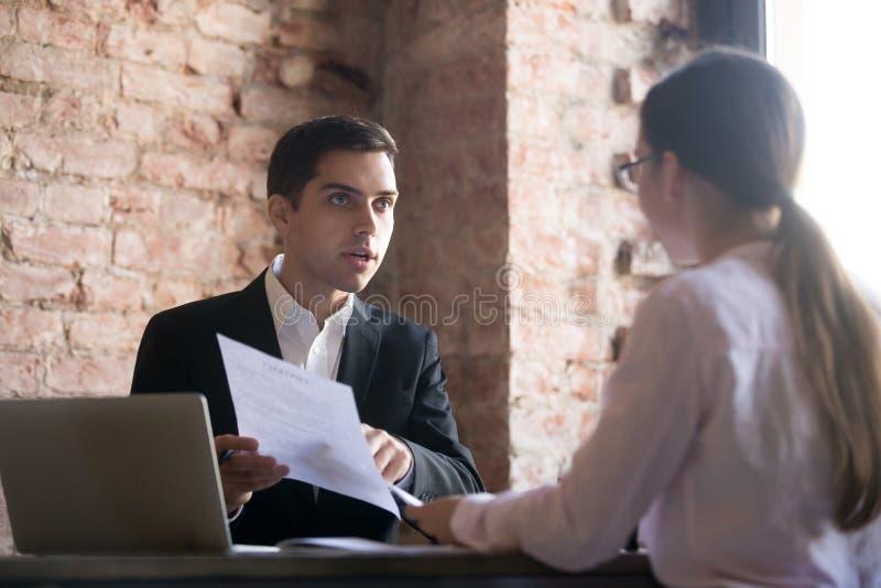 Patron d'outrage parlant à l'employé, indiquant l'erreur dans le document images stock